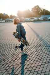 Beautiful young girl in sunglasses walk with skateboard at sunset