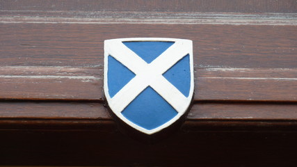shield-shaped wooden symbol with Scottish flag