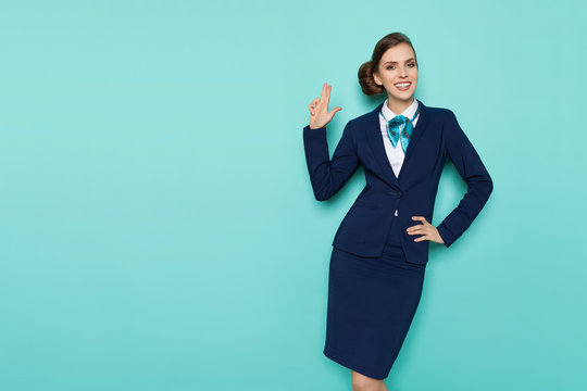 Smiling Stewardess Is Showing Pistol Hand Sign