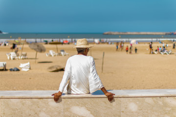 Man in a white tunic and a straw hat sitting on the beach.September 2, 2012 in Essaouira, Morocco, Africa