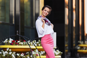 Young fashion business woman in white shirt and pencil skirt walking in city street