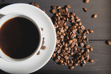 White cup of coffee with coffee beans on black wooden background and sunlight in the morning.