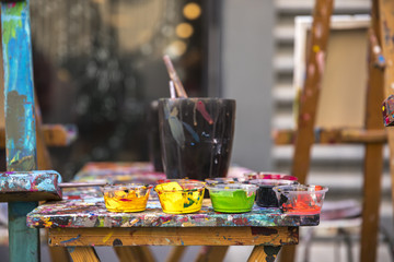 paint and brushes on a clorful table