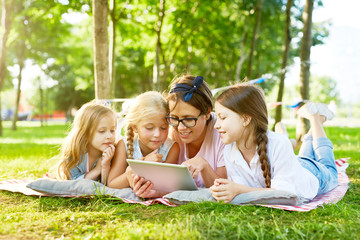 Three cute girls and their teacher with tablet watching curious videos in the net while relaxing outdoors