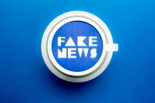 Fake news and HOAX concept. Paper cup with fake news words on blue background.
