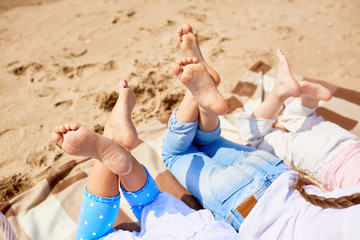 Soles of bare feet of girls lying on sandy beach on hot summer day and enjoying rest