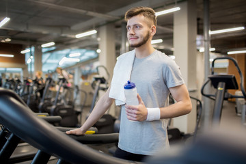 Sporty guy with towel and bottle of water leaning on one of treadmills before or after sports training