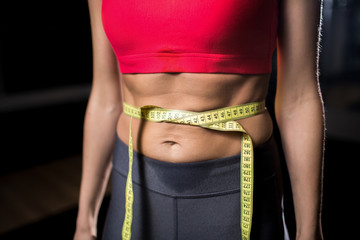Waist of young fit woman in activewear tied with measuring tape