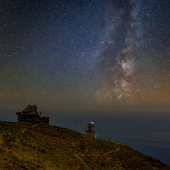 night scene, lighthouse on a marine cape under a milky way