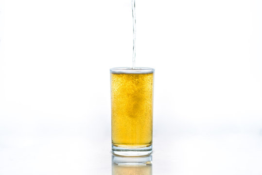 Pour glass of beer on white background