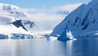 Beautiful Neumayer Channel, Antarctica. Snowcapped mountains, icebergs, calm waters and blue skies