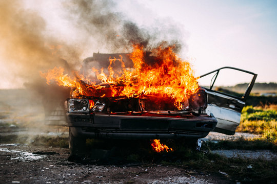 Front of a car burning with a open flames  and dark smoke