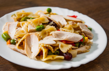 farfalle pasta salad with chicken breast fillet and vegetables in plate on wooden background