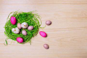 Easter decorations on wooden background with grass, chicken and eggs. Top view.