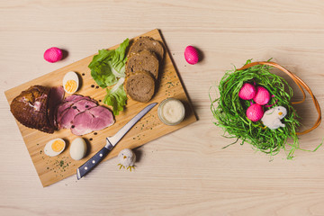 Smoked ham, eggs and bread on wooden board with spices. Easter decorations. Top view.