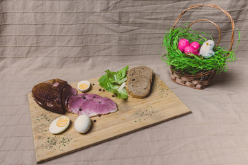 Smoked ham, eggs and bread on wooden board with spices. Easter decorations.