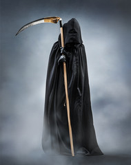 Grim Reaper standing in the fog at night. Photo of personification of death wielding a large scythe in silhouette.