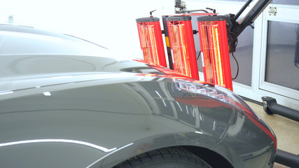 Red lamps for drying the machine after painting or ceramics, gray car body.