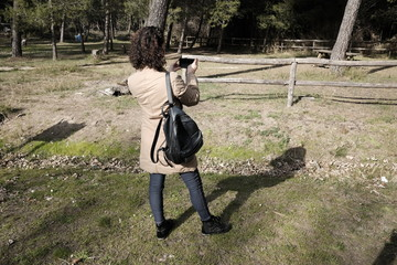 girl photographs flowers in the park