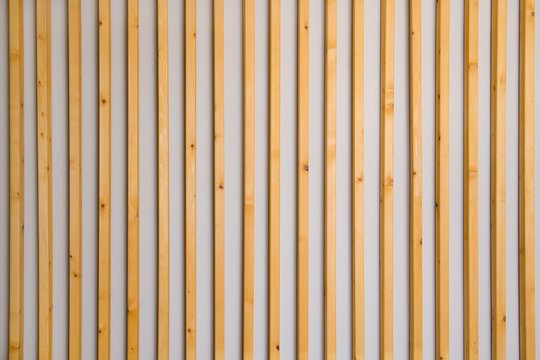 Wooden vertical slats batten on a light gray wall background. Interior detail, texture, background. The concept of minimalism and Scandinavian style in the interior. Copy space
