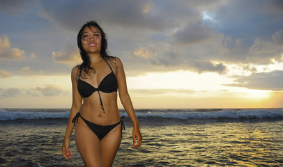 beautiful and sexy young Asian woman with gorgeous body in bikini posing happy on sea water under a Summer sunset  orange sky