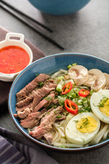 Asian ramen soup with beef, egg, chives and mushrooms in bowl.