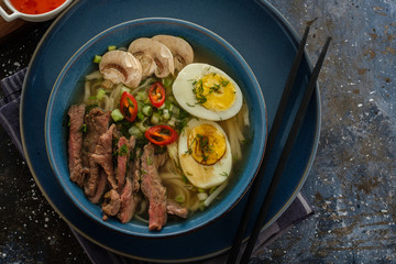 Asian ramen soup with beef, egg, chives, mushrooms in bowl on dark background.
