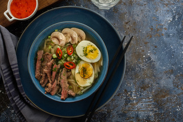 Asian ramen soup with beef, egg, chives, mushrooms in bowl on dark background. Copyspace. Top view