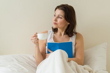 Smiling middle-aged woman reading book and holding cup with coffee on the bed