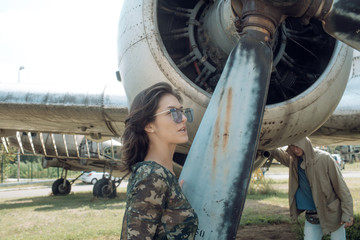 Girl in camouflage shirt near propeller and turbine of old plane on sunny day. Military woman, pilot on aerodrome. Couple on excursion at aviation museum, husband tired of walking. Air forces concept.