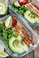 Healthy meal prep containers with rukola, turkey grill, tomatoes and avocado