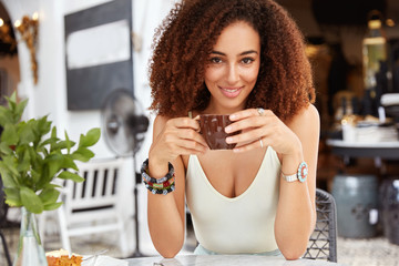 Pretty adorable woman has curly hair wears casual clothing, keeps cup in hands with aromatic coffee, sits against cozy restaurant, has break after work. Lovely dark skinned female with Afro hairdo