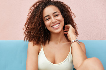 Photo of positive smiling woman with broad charming smile dressed casually and recreats at home, feels relaxed and comfortable, happy to hear good news from friend. People, ethnicity, happiness