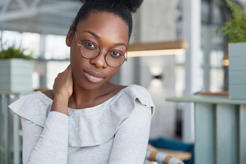 Beautiful dark skinned clever female student in big round eyewear, feels tired after preparing for exams, looks confidently into camera. People, ethnicity, facial expressions and lifestyle concept
