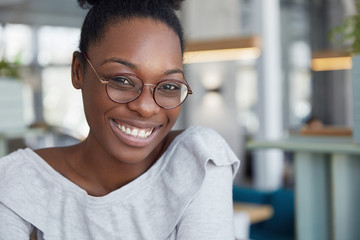 Headshot of positive attractive dark skinned African female in round glasses, expresses pleasant emotions, feels happy after recieving praise from boss for successfully done work or project.