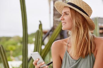 Sideways portrait of happy lovely woman with dreamy positive look, wears summer hat, holds smart phone as messages with friends and checks notification, spends free time in outdoor bar or cafe