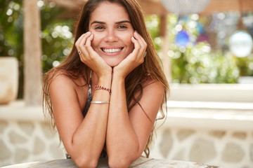 Portrait of happy tanned brunette female with long hair, perfect white teeth and pleasant smile, sits against cafe interior. Relaxed woman recreats abroad during summer vacations. People and beauty