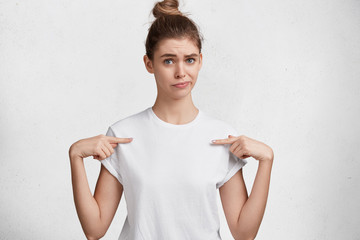 Indoor shot of unhappy young cute woman with blue eyes, hair knot, dressed in casual white t shirt, indicates at blank copy space of t shirt, advertizes clothing, isolated over studio background.