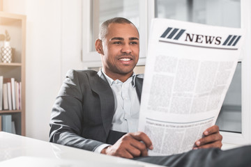 Portrait of young african guy reading newspaper. Man in respectable suit sitting near table and smiling