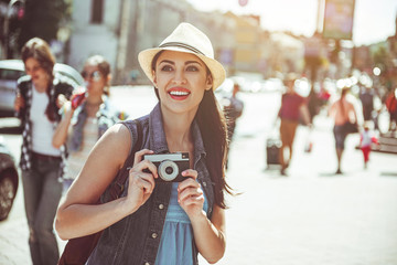 Obraz Portrait of pleased young woman doing images by camera while looking sightseeing. Glad tourist walking concept - fototapety do salonu