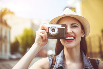 Outgoing woman doing images by camera while going along street. Beaming lady during trip concept