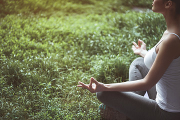 Peaceful woman meditating while sitting in park. She locating in lotus posture. Copy space. Relax concept
