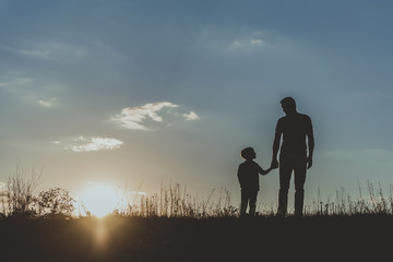 Silhouette of father and son standing on grass and holding hands against blue sky background. Copy space in left side