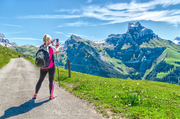 A woman tourist with sticks for a walk and a backpack, lagged behind the group, takes pictures of the peaks and landscape of the Swiss Alps. Swiss ski resort Engelberg in summer