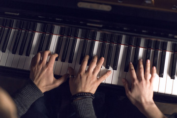 Hands of the pianist on the piano