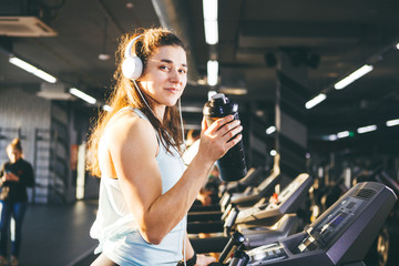 Sports nutrition and exercise. beautiful woman holds protein in her hand in bottles, shaker, listens music in headphones on head in gym running on treadmill, at hands of sports watch,in sunny weather