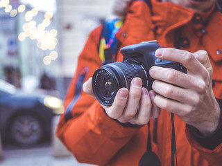 close up portrait of man holding dslr camera in his hands