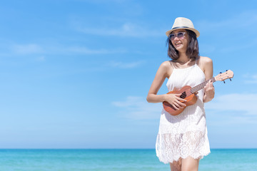 Happy summer vacation on the beach. Pretty young woman playing ukulele with smiling and blue sky background. Picture for add text message. Backdrop for design art work.