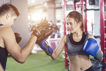 Man trainer holding sport mitts in gym and female box gloves. Boxing workout woman in fitness class room.Sport boxing exercise.