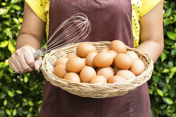 Young woman holding basket of Fresh Chicken Eggs